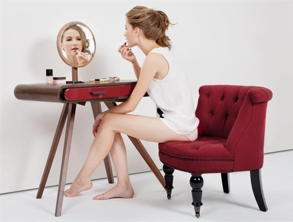 Feminine-Dressing-Table-With-Elegant-Design-La luminosità della lacca rossa dona un tocco glamour alle finiture in noce della struttura. Lo specchio rotondo e le gambe inclinate completano l'armonia con un continuo gioco di linee e rotondità.