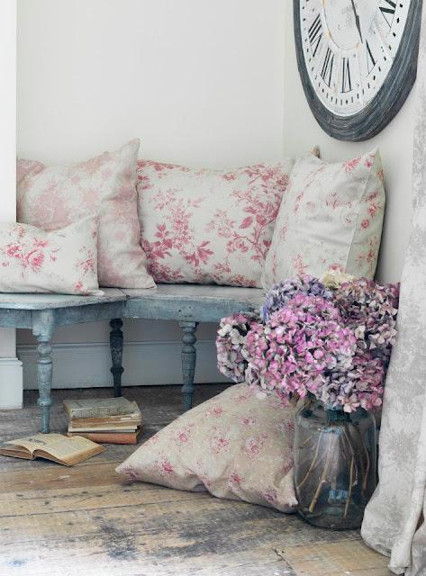 un angolo adorabile dal gusto francese con un vecchio grande orologio alla parete e tanti cuscini con fantasie floreali