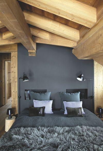 In una camera con soffitto travi a vista, la parete grigia dietro al letto, può assumere anche un aspetto rustico.